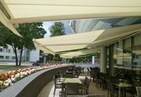 Minimālistiskas un vienkrāsainas markīzes lieliski sader ar modernu, īpašas formas ēkas fasādi